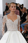 Model walks runway in a long sleeve beaded bridal gown and embroidered illusion corset from the Dennis Basso for Kleinfeld 2018 Bridal Collection on October 5 2017, during New York Bridal Fashion Week.