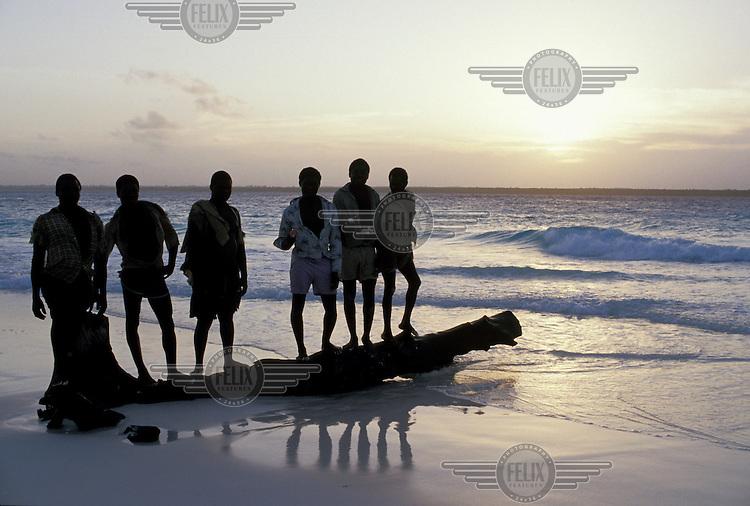 Youths on the beach at dusk.