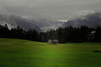 Cattle shed in  a meadow, background of clouds and mountains. Imst district, Tyrol/Tirol, Austria, Alps.