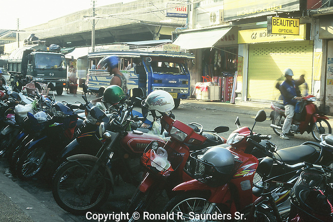 STREET IN PHUKET THAILAND LINED WITH MOTORCYCLES AND BUSES