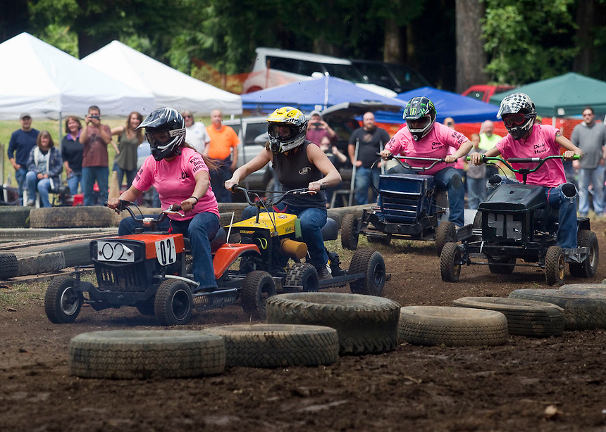 """The Powder Puff lawn mower race takes place at the annual """"Territorial Days"""" festival in Amboy Sunday July 10, 2016. Other events during the celebration included a logging show, musical performances, an art show and a carnival. The celebration highlights the area's connection to logging and pioneering.  (L to R) Lindsey Davis, Courtney Nicholson, Skylar Riggs, and Emily Hoffman. (Photo by Natalie Behring/ for the The Columbian)"""