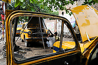 INDIA West Bengal, Kolkata, open garage in Elgin Road , open air repair of a HM Ambassador yellow cab, the car is still produced new at Hindmotor factory after license of Oxford Morris  / INDIEN Westbengalen Kalkutta, offene Kfz Werkstatt in der Elgin Road , Reparatur eines Ambassador Taxi , der HM Ambassador laeuft heute noch neu nach Vorlage des Oxford Morris bei HM Hindustan Motors vom Band