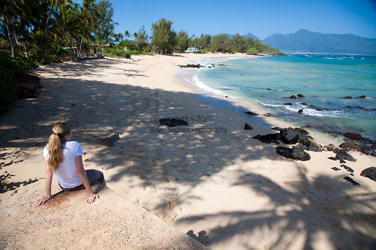 Paia Inn on the North Shore of Maui.  This hotel is located in a  quiet beachfront community and has a private entrance to Paia Bay.  Here a woman rests and takes in the view of Paia Bay and the West Maui Mountains.