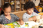 Education preschool 3-4 year olds boy and girl sitting side by side boy stacking pieces of puzzle blocks, girl playing with puzzle with wooden pieces