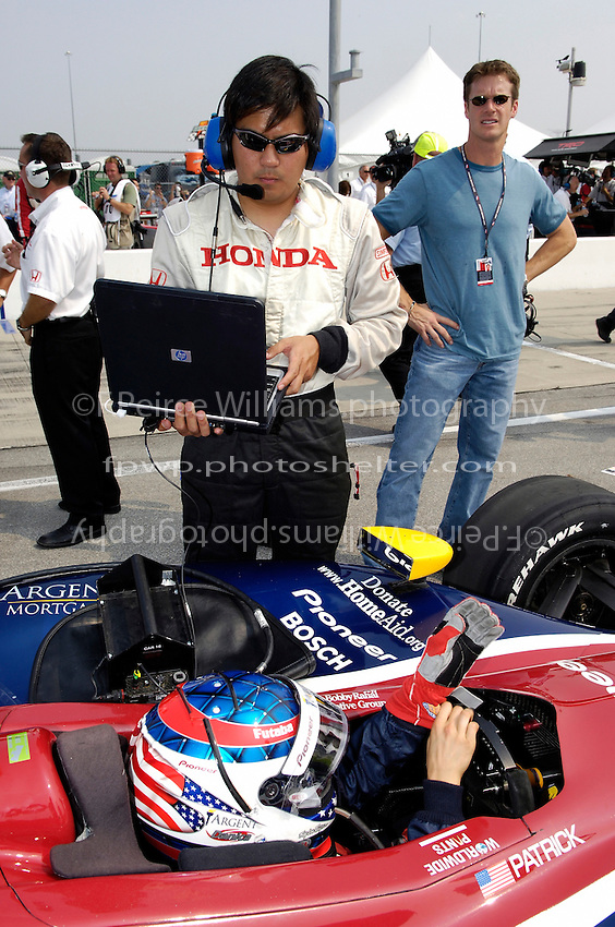 11 September, 2005, Joliet,IL,USA<br /> Danica Patrick puls her gloves on as a Honda engineer looks on.<br /> Copyright&copy;F.Peirce Williams 2005