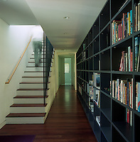 A long bookcase runs the entire length of the house and is the unifying feature between all the living spaces