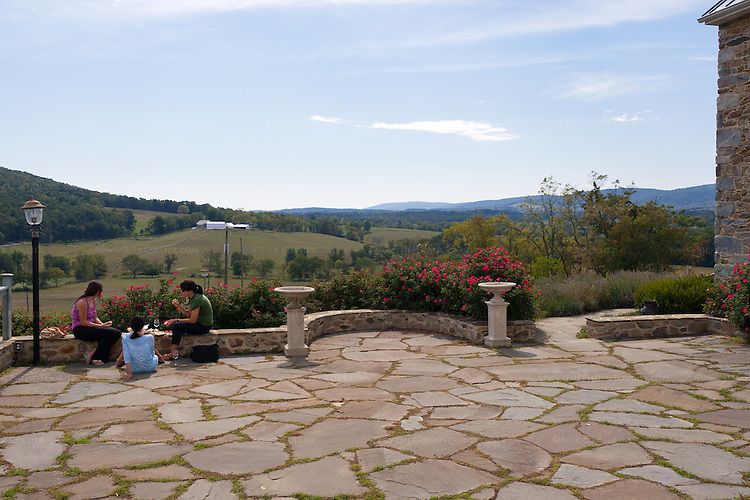 Visitors enjoy a snack and wine, sitting around the low wall bordering the patio to enjoy the valley view beyond at Hillsborough Vineyards.