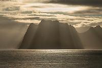 Rays of light shine over Skolmen mountain peak, Vestvågøy, Lofoten Islands, Norway