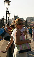 Czeck Republic - Prague, Young woman smiles enjoying the passing crowds and sun on the Charles Bridge