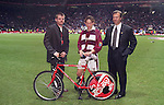 Poor dejected Hearts player Neil McCann gets a pushbike from the sponsors as the victorious Rangers team celebrate with the trophy in the 1996 Coca-Cola League Cup Final partying behind him in front of the Rangers support at Celtic Park.