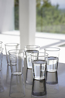 A collection of glass tumblers sit on a grey work-surface, some of which are half filled with water.