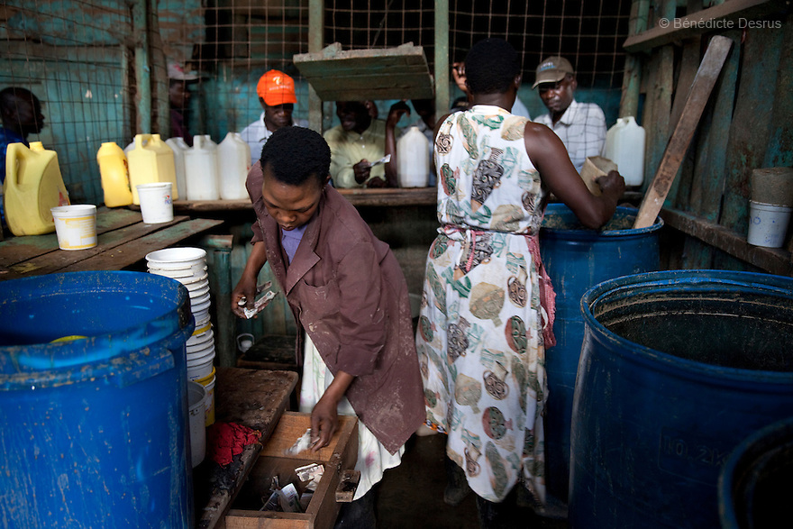 Alice(L) and Mary(R) working at the Madiaba Busaa Club in a Nairobi slum on april 7, 2013. Both have been selling Busaa, a traditional fermented beer, for many years. Busaa is made by crudely fermenting maize, millet, sorghum or molasses. At Kshs 35 per liter it is much cheaper than a Kshs120 half-liter bottle of commercial beer. The local brew was legalised in 2010 and since then busaa clubs have become increasingly popular. Drinking is on the rise in Kenya, especially among young people. Photo by Benedicte Desrus