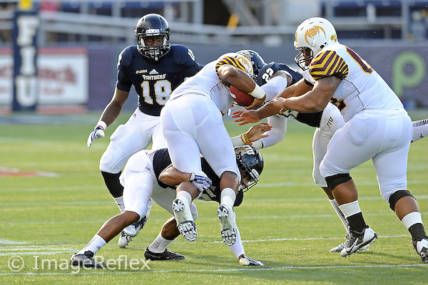 14 September 2013:  FIU cornerback Sam Miller (39) upends Bethune-Cookman running back Anthony Jordan (4) in the first quarter as the Bethune-Cookman Wildcats defeated the FIU Golden Panthers, 34-13, at FIU Stadium in Miami, Florida.