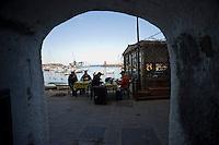 Alcune persone sedute nel porto del Giglio con sullo sfondo visibile la nave da crociera Costa Concordia..People seat as the cruise liner Costa Concordia aground in front of the harbour of the Isola del Giglio (Giglio island) after hitting underwater rocks..