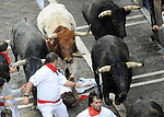 Participants run with Miura´s bulls during the last bull run in the San Fermin Festival on July 14, 2014, in Pamplona, Basque Country. Every year, tens of thousands of people pack Pamplona's streets for a drunken kick-off to one os worls's best-known fiesta: the nine-day San Fermin bull-running festival. (Ander Gillenea / Bostok Photo)