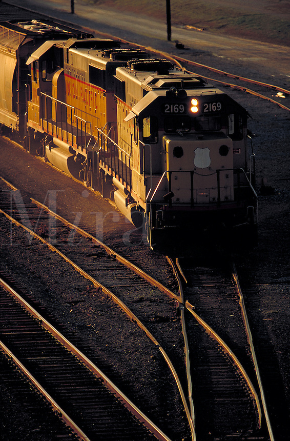 locomotive on converging tracks at sunset