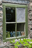 The woodwork of the farmhouse has been painted a subtle olive green to complement the rough stone walls of the exterior