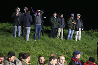 Spectators stand on a grass bank to watch the game during Maldon & Tiptree vs Newport County, Emirates FA Cup Football at the Wallace Binder Ground on 29th November 2019