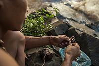 A fisherman threads earthworms on his fishing line in front of the Khone Phapheng falls. 04/08/2013 © Thomas Cristofoletti / Ruom