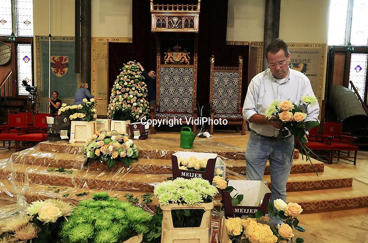 Foto: VidiPhoto<br /> <br /> DEN HAAG - Naast de troon van Koning Willem-Alexander in de Ridderzaal in Den Haag, wordt maandag koortsachtig gewerkt aan bloemenversieringen. Onder leiding van de Scheveningse bloemist Ton Verzijl (foto), worden zowel naast de troon als langs de houten lambrizeringen decoraties van chrysanten en rozen aangebracht voor Prinsjesdag. De bloemen zijn afkomstig van chrysantenkweker Ronald Olsthoorn uit De Lier en rozenkweker Wesley Meijer uit Delfgauw. In totaal worden bijna 3000 pluischrysanten en grootbloemige rozen gebruikt. Dit jaar is gekozen voor witte en roze tinten. Na Prinsjesdag worden de bloemwerken bij diverse verzorgings- en verpleeghuizen in de regio Den Haag aangeboden.