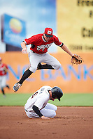 Carolina Mudcats shortstop Reed Harper (17) jumps over Jonah Heim (6) sliding into second base, after throwing to first, during a game against the Frederick Keys on June 4, 2016 at Nymeo Field at Harry Grove Stadium in Frederick, Maryland.  Frederick defeated Carolina 5-4 in eleven innings.  (Mike Janes/Four Seam Images)