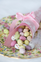 A pink paper cone filled with small, speckled chocolate Easter eggs in a variety of pastel colours on a pretty plate
