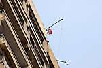 "An Egyptian flag with the words ""Egypt's Revolution, the 25th of January"" flies over the Israeli embassy after a protester managed, at dawn, to climb 15 floors on a building where the Israeli embassy is located to remove the Israeli flag from the embassy balcony and replace it with the Egyptian flag in in Cairo August 21, 2011. Egypt and Israel sought on Sunday to defuse a diplomatic crisis over the killing of five Egyptian security personnel during an Israeli operation against cross-border raiders, but crowds of Egyptians protested at the Israeli embassy in Cairo overnight. Photo by Ahmed Asad"
