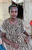 DJIBOUTI , Obock, refugee camp Markazi for yemeni war refugees , woman in striped dress / DSCHIBUTI, Obock, Fluechtlingslager Markazi fuer jemenitische Fluechtlinge