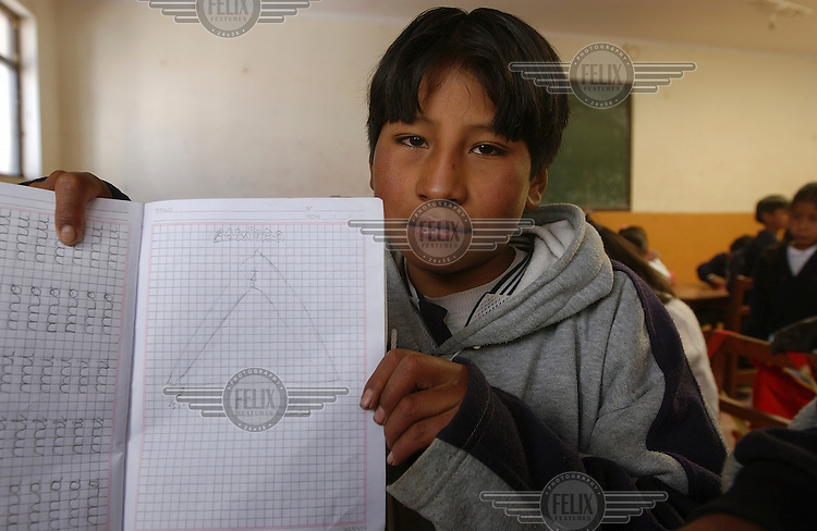 12 year old Jose Lucas Benabides displays his exercise book at San Cristobal school, in a classroom which he shares with his younger siblings.  He attends school only sporadically on account of working in the silver mines to subsidise his mother's earnings and consequently struggles to keep up with his younger classmates.  His late father was a miner who died 5 years ago of silicosis, a respiratory disease caused by the inhalation of silica dust.  Cristobal school is part of a CARE International project to educate children in the region and offer them the opportunity not to work in the mines...Photo: Dermot Tatlow/Panos Pictures/Felix Features