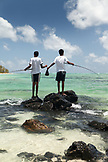 MAURITIUS, twin boys fish side by side off of some rocks, Iles aux Cerfs Island