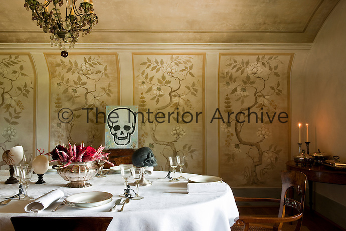 Delicate trompe l'oeils painted on the curved wall of a dining room with a laid table