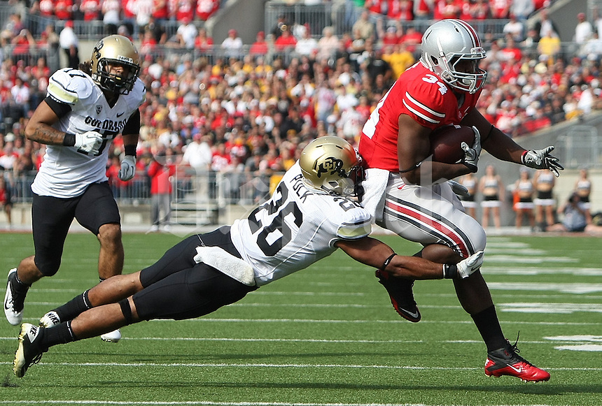 Ohio State Buckeyes running back Carlos Hyde (34) tries to get away from Colorado Buffaloes defensive back Ray Polk (26) in the first quarter of their NCAA football game at the Ohio Stadium in Columbus, September 25, 2011.  (Dispatch photo by Neal C. Lauron)
