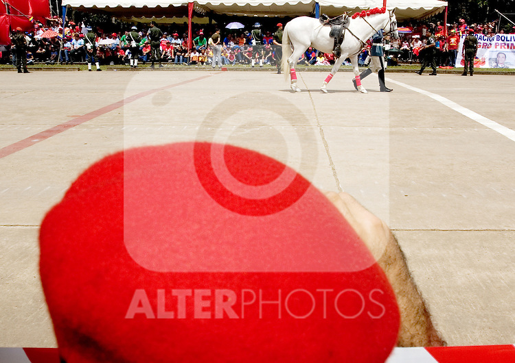 "A Venezuelan soldier wearing a red beret watches a horse that represents Simon Bolivar's white horse during a military parade in Valencia, Venezuela, on Saturday, June 24, 2006. The military parade was to celebrate Army Day and took place in ""Campo de Carabobo"", the field where the last big battle for the Venezuelan independence was won. (ALTERPHOTOS/Alvaro Hernandez)."