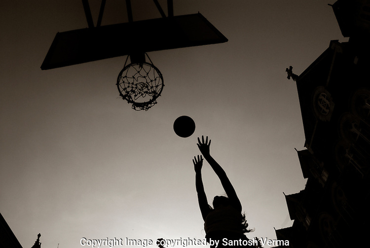 A college athelet at practise at the basketball net, surrounded by the architecture of the institute adorned with the cross as if echoing the words of encouragement 'DEI GLORIAM' -for the Glory of God. Photograph © Santosh Verma