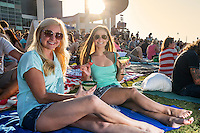 Two attractive Austin local females enjoy drinks at an outdoor movie night in downtown Austin, Texas.