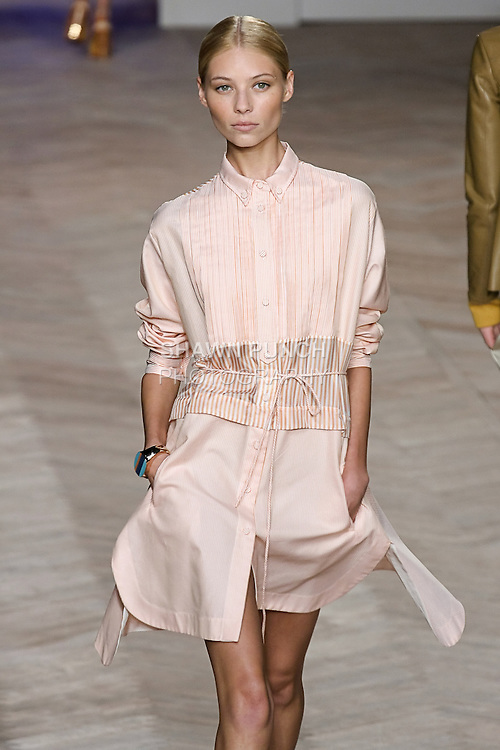 Vika Falileeva walks the runway in a orange/white multi-striped cotton long-sleeved shirtdress with shirttail hem and pleated bib, by Tommy Hilfiger for the Tommy Hilfiger Spring 2012 Pop Prep Collection, during Mercedes-Benz Fashion Week Spring 2012.