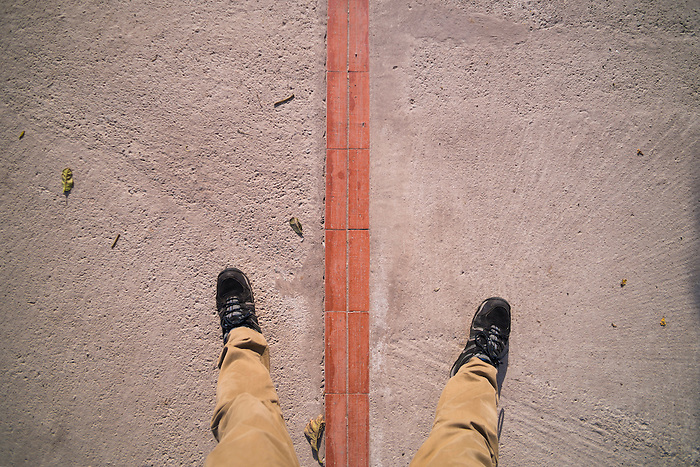 One foot on either side of the Equator at the 'Middle of the World', San Antonio de Pichincha, Quito, Ecuador, South America