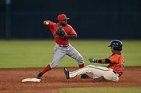 AZL Angels shortstop Kendy Moya (3) makes a throw to first base as Luis Toribio (22) slides into second base during a game against the AZL Giants Orange at Giants Baseball Complex on June 17, 2019 in Scottsdale, Arizona. AZL Giants Orange defeated AZL Angels 8-4. (Zachary Lucy/Four Seam Images)