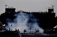 Sep 28, 2013; Madison, IL, USA; NHRA pro stock driver Mike Edwards (left) does a burnout alongside Shane Gray during qualifying for the Midwest Nationals at Gateway Motorsports Park. Mandatory Credit: Mark J. Rebilas-