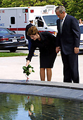 First lady Laura Bush places a bouquet of flowers  at the Reflecting Pond of the Women's War Memorial as United States President George W. Bush looks on at Arlington National Cemetery in Arlington, Virginia on Memorial Day, May 28, 2001.  The Presidential motorcade made an unscheduled stop at this memorial of the return from Arlington Cemetery.    <br /> Credit: Dennis Brack - Pool via CNP