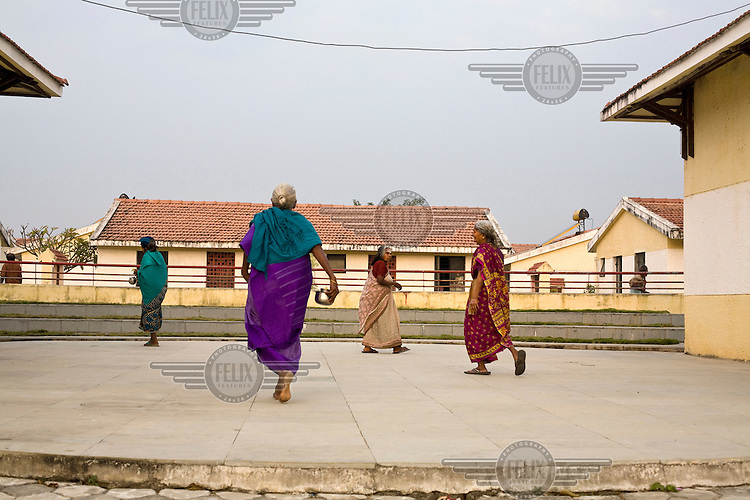 Four elderly women walk across a small amphitheatre after morning worship at the Tamaraikulum Elders' village. The village is a pioneering experiment initially set up by HelpAge India after the Asian Tsunami to help elderly people displaced by the natural disaster. Today, the village is a self-sustaining community providing a family environment where more able-bodied residents assist the less able-bodied and provides 100 older people with a safe place to live, free healthcare, emotional security, a good diet and professional care and support...