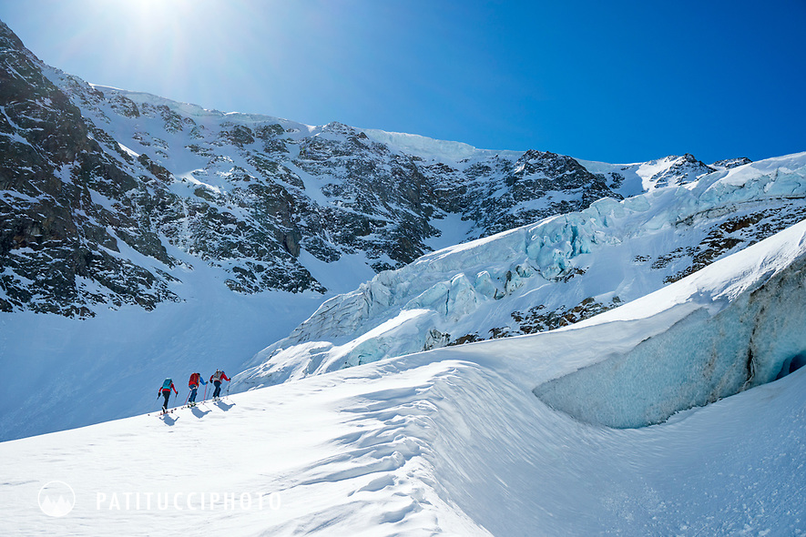 A group ski touring from the Susten Pass to the Tierbergli Hut while on the Berner Haute Route, Switzerland.