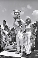 Gordon Johncock lifts the trophy after winning a 1976 USAC Champ Car race at Michigan International Speedway near Brooklyn, Michigan, USA.