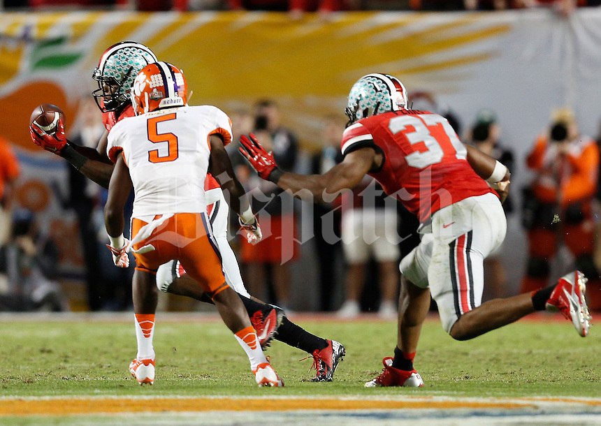 Ohio State Buckeyes safety C.J. Barnett (4) intercepts a pass in the fourth quarter of the Discover Orange Bowl between Ohio State and Clemson at Sun Life Stadium in Miami Gardens, Florida, Saturday night, January 4, 2014.The Clemson Tigers defeated the Ohio State Buckeyes 40 - 35.(The Columbus Dispatch / Eamon Queeney)