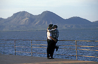 Young lovers embracing and kissing on the Malecon promenade in  Managua, Nicaragua. Lake Xolotlan is in the background.