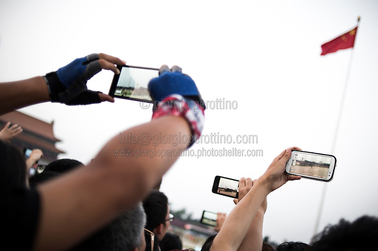 Chinese people take pictures using their smartphones during the daily Chinese Army parade of the flag raising in Tiananmen Square in Beijing, China, July 19, 2014.<br /> <br /> Smartphones are an essential tool of Chinese ordinary life. Everywhere in China, people use them to take pictures to share online, to talk and chat, to play videogames, to get access to the mainstream information, to get connected one each other. In the country where the main global social media are forbidden - Facebook, Twitter and Youtube are not available  -, local social networks such as WeChat have a wide spread all over the citizens. The effect is an ordinary and apparently compulsive way to get easy access to digital technology and modern way of communication. <br /> A life through the display. Yes, We Chat.<br /> <br /> © Giorgio Perottino