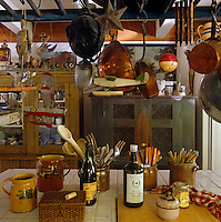 Copper pots and model aeroplanes hang from a wooden rack above the tiled kitchen work surface