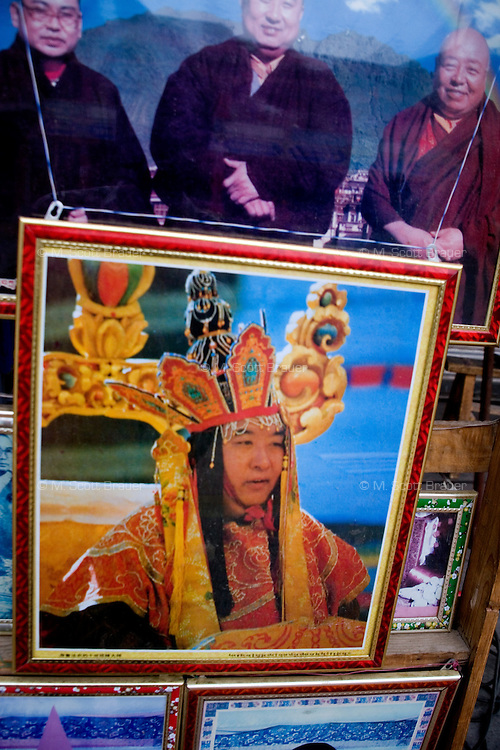 Images of monks, religious leaders, lamas, and religious art are on display at a shop for pilgrims and monks in Xiahe, Gansu, China.  Xiahe, home of the Labrang Monastery, is an important site for Tibetan Buddhists.  The population of the town is divided between ethnic Tibetans, Muslims, and Han Chinese.