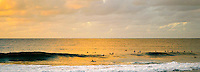 sunset and clouds over surfers in the calm tropical ocean water