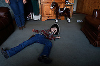 "Dressed as a cowboy, Sheriff Tanner Lauman is ""shot dead"" on the living room floor in a moment of play.<br />